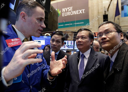 Dinh Tien Dung Vietnam's Finance Minister Dinh Tien Dung, second from right, visits the trading post of specialist Jason Hardzewicz on the floor of the New York Stock Exchange, . Stocks opened higher as traders were encouraged by a pickup in retail sales and more signs of health in the U.S. job market