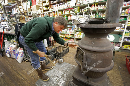 Stock Picture of David Blackley David Blackley stokes the fire in the pot belly stove at Renfrow Hardware in Matthews, N.C., as a winter storm hit the area