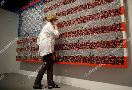 """Jana Millstone Jana Millstone, of Lancaster, Pa., wears Google Glass to view artwork with the design of the US flag titled """"Viewpoints of Billions"""" by artist David Datuna, in the Design District neighborhood of Miami. The piece is the first of a series which combines art and technology using Google Glass to create an interactive experience. The piece was unveiled for Art Basel in Miami Beach which runs from Dec. 5-8"""