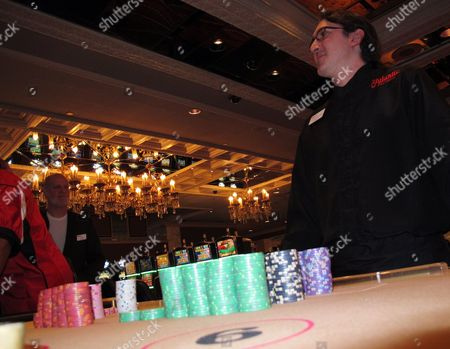 This, photo shows dealer Chris Schmalzel waiting for security staff to take the stacks of gambling chips at his table at the Atlantic Club Casino Hotel minutes after the casino shut down in Atlantic City, N.J. Three former executives at the shut-down Atlantic Club Casino Hotel have found new jobs with one of the companies that bought and closed the casino