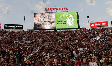 A tribute to Associated Press photographer Dave Martin is seen on the scoreboard at the Rose Bowl before the NCAA BCS National Championship college football game between Auburn and Florida State, in Pasadena, Calif