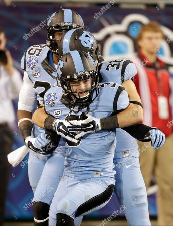 Ryan Switzer, Damien Washington, Ryan Mangum North Carolina's Ryan Switzer, front, celebrates with teammates Damien Washington, back, and Ryan Mangum, center, after returning a punt for a touchdown against Cincinnati during the second half of the Belk Bowl NCAA college football game in Charlotte, N.C
