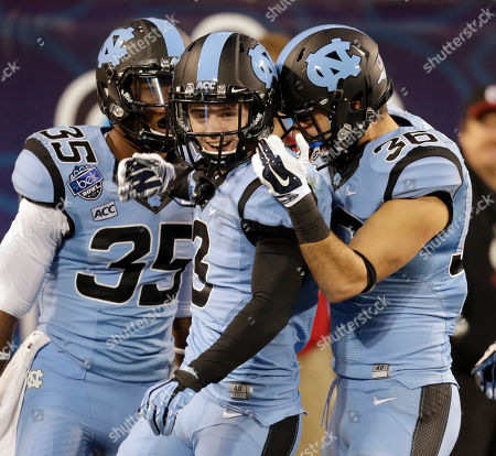 Stock Photo of Ryan Switzer, Damien Washington, Ryan Mangum North Carolina's Ryan Switzer, center, celebrates with teammates Damien Washington, left, and Ryan Mangum, right, returning a punt for a touchdown against Cincinnati during the second half of the Belk Bowl NCAA college football game, in Charlotte, N.C