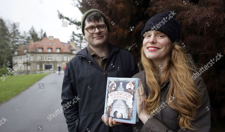 """Colin Meloy, Carson Ellis This photo shows Colin Meloy, left, front man and songwriter for the indie folk band, The Decemberists, and his illustrator wife, Carson Ellis, with their latest book in front of Pittock Mansion in the west hills of Portland, Ore. The couple have just published the third installment of a popular adventure book series for middle-schoolers called the """"Wildwood Chronicles."""" The third volume is titled """"Wildwood Imperium"""