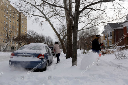Cecy Wang, left, clears snow off her car as Samuel Scott, right, shovels a sidewalk, in St. Louis. As Missourians muddled through another frigid day Tuesday, the worst cold snap in nearly two decades was about to come to an end but many roads remained partly snow-covered two days after a winter storm dumped several inches of snow