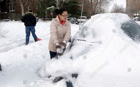 Cecy Wang, right, clears snow off her car as Samuel Scott, left, shovels a sidewalk, in St. Louis. As Missourians muddled through another frigid day Tuesday, the worst cold snap in nearly two decades was about to come to an end but many roads remained partly snow-covered two days after a winter storm dumped several inches of snow