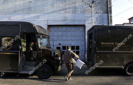 UPS delivery workers move packages from one truck to another, in Newark, N.J. UPS spokeswoman Natalie Black said air and international customers who didn't receive their packages on time are entitled to a refund under its service agreements. Such guarantees, however, were suspended for ground packages shipped after Dec. 10. Black said a small percentage of packages were delayed due to numerous factors, including an air network that exceeded its capacity, poor weather and a shortened Christmas shopping season