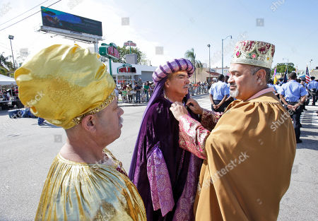 "Gabriel Lopez, Salvador Cajete, Oscar Vasquez Dressed as the Three Wise Men, Oscar Vasquez, right, fixes the costume of Salvador Cajete, center, as he chats with Gabriel Lopez before marching in the Three Kings Day Parade, in Miami. The parade which honors the Three Wise Men, traveled down ""Calle Ocho,"" in Miami's Little Havana neighborhood"