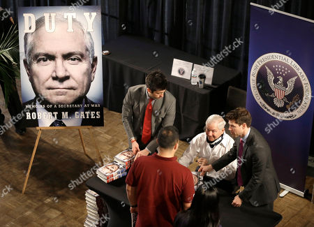 Stock Photo of Robert Gates Wearing a neck brace after a fall a few weeks ago former defense secretary Robert Gates, second from left, signs copies of his new book after speaking at Texas A&M University, in College Station, Texas