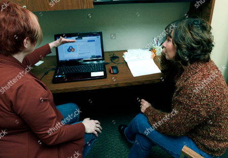 In this photo, Caring Hearts Clinic director Sue Cook, left, helps Kathy Bannister with enrolling in the Affordable Care Act at the free clinic in Marlette, Mich