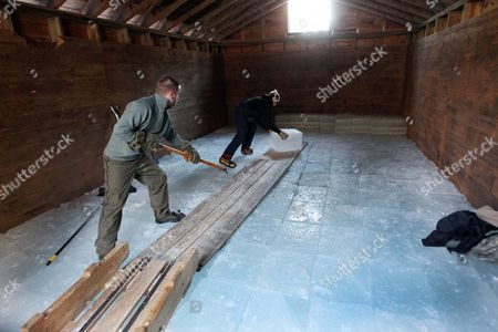 Stock Photo of Douglas Adams, left, and Parker Hansen stacks ice in the ice house at the Rockywold-Deephaven Camp in Holderness, N.H. . For more than a century ice from Squam Lake has been used to keep ice boxes cool for summer residents at the camp