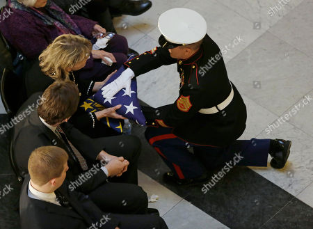 A member of the Honor Guard hands the American flag that covered the casket of former Indiana Congressman Andrew Jacobs Jr. to widow Kim Hood Jacobs during a funeral service at the Statehouse, in Indianapolis. Jacobs died Saturday, Dec. 28, 2013, at age 81