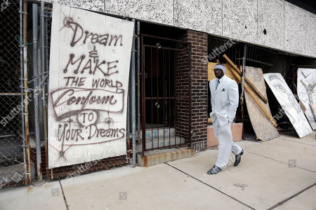 Melvin White, founder of the Beloved Streets of America project, walks past a boarded up building during a tour of Dr. Martin Luther King Jr. Drive in St. Louis. The nonprofit is working to revitalize a downtrodden six-mile stretch of the drive named for the slain civil rights leader, marked by vacant lots, crumbling buildings and a preponderance of liquor stores, pawn shops and check-cashing businesses. Project leaders hope revitalize MLK's streets that have fallen into disrepair in cities around the country. (AP Photo/Jeff Roberson