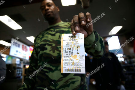 John Hollis shows off his Mega Millions lottery ticket he purchased at the Fuel City convenience story, in Dallas. The Mega Millions jackpot soared to $586 million on Monday amid a frenzy of ticket purchases, a jump that pushed the prize closer to the $656 million U.S. record set last year