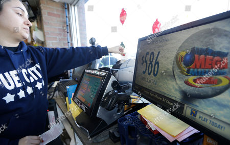 Karen Rodriguez prints out a Mega Millions lottery ticket at the Fuel City convenience story, in Dallas. The Mega Millions jackpot soared to $586 million on Monday amid a frenzy of ticket purchases, a jump that pushed the prize closer to the $656 million U.S. record set last year