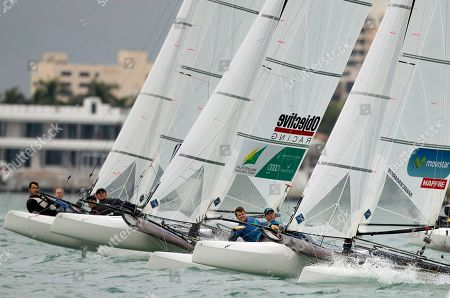 Pippa Wilson and John Gimson, left, from Great Britain, Jason Waterhouse and Lisa Darmanin, center, from Australia, and Iker Martinez and Tara Pacheco, right, from Spain, make the turn during a World Cup sailing race, in Miami