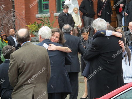 Nancy Montgomery, center, whose husband Jim Lovell was killed in a New York City train derailment, embraces a mourner after Lovell's funeral in Cold Spring, N.Y., on . Lovell and three others died when the Metro North commuter train he was riding in derailed and tumbled off the tracks on Sunday, morning, Dec. 1. Sixty others were injured in the accident