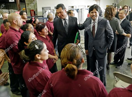 """Stock Photo of Alex Padilla, Kevin DeLeon California State Sens. Alex Padilla, left, and Kevin DeLeon greet workers at the Command plastics recycling plant before a news conference to announce a possible agreement in the California legislature that could lead to a statewide ban on carry-out plastic bags at supermarkets, liquor stores and pharmacies by 2016, in Vernon, Calif., . Lawmakers in Sacramento have debated similar proposals for years, facing opposition from manufacturers that produce billions of plastic shopping bags each year. The agreement calls for using $2 million for loans and grants that could help those companies retrain workers and convert to manufacturing """"a new generation of reusable bags with the smallest environmental footprint,"""" a summary of the legislation said. Los Angeles and nearly 100 other cities and counties in the state have enacted bans on single-use plastic bags at stores"""