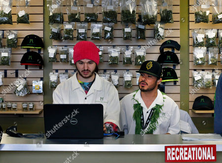 """Stock Picture of Employees David Marlow, right, and Chris Broussard work behind sales counter inside Medicine Man marijuana retail store, which opened as a legal recreational retail outlet in Denver on . Colorado began retail marijuana sales on Jan. 1, a day some are calling """"Green Wednesday"""