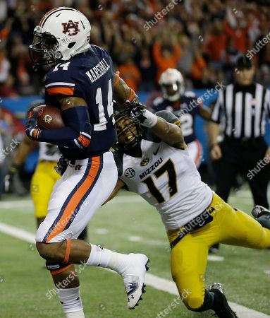 Auburn quarterback Nick Marshall (14) runs into the end zone for a touchdown against Missouri safety Matt White (17) during the first half of the Southeastern Conference NCAA football championship game, in Atlanta