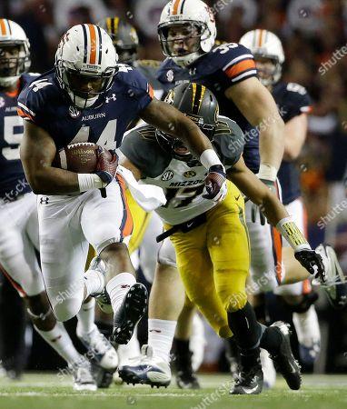 Auburn running back Cameron Artis-Payne (44) runs against Missouri safety Matt White (17) during the second half of the Southeastern Conference NCAA football championship game, in Atlanta