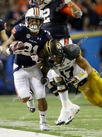 Auburn running back Tre Mason (21) runs against Missouri safety Matt White (17) during the second half of the Southeastern Conference NCAA football championship game, in Atlanta