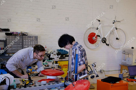 Mechanical and software engineer Julian Fong, right, and vehicle design engineer Jon Stevens work on a development to the Copenhagen Wheel, red disk, a human/electric hybrid bicycle engine at Superpedestrian in Cambridge, Mass