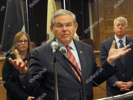 Stock Photo of U.S. Sen. Robert Menendez, D-N.J., speaks at a a public hearing on flood insurance rates, in Brick Township, N.J. Peggy Molloy, left, who fears that skyrocketing flood insurance premiums will force her from her Point Pleasant home, and Brick Township Mayor John Ducey, right, stand in background. Menendez is pushing a bill that would delay drastic flood insurance rate increases for up to two years while the federal government studies their affordability and the science behind them