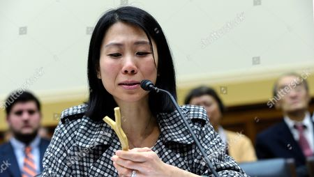 "Stock Picture of Danielle Wang Danielle Wang, daughter of Wang Zhiwen, holds a piece of wood that was polished by her father during his imprisonment while testifying on Capitol Hill in Washington, before the House Foreign Affairs Committee hearing entitled: ""Their Daughters Appeal to Beijing: 'Let Our Fathers Go"