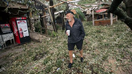 Crab Shack restaurant owner Jack Flanagan walks through the outside dining area of his business near Tybee Island, Ga., after winds and storm surge from Hurricane Matthew hit the small community along the east coast of Georgia