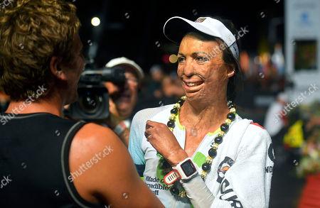 Stock Image of Turia Pitt Bush fire survivor Turia Pitt, right, of Australia, gets a hug after finishing the Ironman World Championship Triathlon, in Kailua-Kona, Hawaii