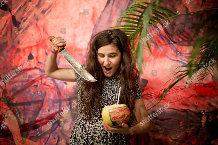 """Naomi Fisher Naomi Fisher """"jokes around"""" after opening a coconut as part of her installation, """"Paradise Walking"""" at Art Basel In Miami Beach show, in Miami Beach, Fla. The show features 285 international galleries drawn from 31 countries, and runs from Dec. 4 to Dec. 8"""
