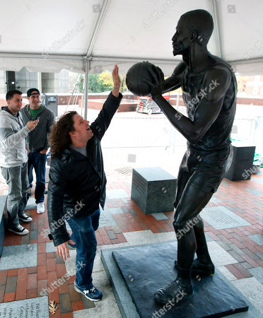 Bill Russell Scott Damgaard, of Boston, reaches up to a statue of former Boston Celtics basketball star Bill Russell after it was unveiled at City Hall Plaza in Boston