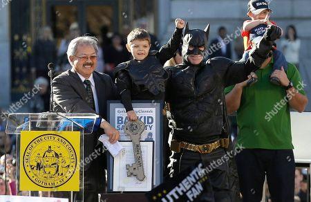 """Miles Scott, dressed as Batkid, second from left, raises his arm next to Batman at a rally outside of City Hall with Mayor Ed Lee, left, and his father Nick and brother Clayton, at right, in San Francisco, . Scott was called into service on Friday morning by San Francisco Police Chief Greg Suhr to help fight crime, as San Francisco turned into Gotham City as city officials helped fulfill the 5-year-old leukemia patient's wish to be """"Batkid,"""" The Greater Bay Area Make-A-Wish Foundation says. He was diagnosed with leukemia when he was 18 months old, finished treatment in June and is now in remission, KGO-TV reported"""