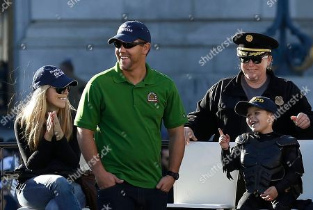 """Miles Scott, dressed as Batkid, bottom right, smiles at a rally outside of City Hall with his parents, Natalie and Nick, and San Francisco Police Chief Joanne Hayes-White in San Francisco, . Scott was called into service on Friday morning by San Francisco Police Chief Greg Suhr to help fight crime, as San Francisco turned into Gotham City as city officials helped fulfill the 5-year-old leukemia patient's wish to be """"Batkid,"""" The Greater Bay Area Make-A-Wish Foundation says"""