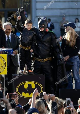 """Miles Scott, dressed as Batkid, second from left, raises his arm next to Batman at a rally outside of City Hall with Mayor Ed Lee, left, and his mother Natalie Scott in San Francisco, . Scott was called into service on Friday morning by San Francisco Police Chief Greg Suhr to help fight crime, as San Francisco turned into Gotham City as city officials helped fulfill the 5-year-old leukemia patient's wish to be """"Batkid,"""" The Greater Bay Area Make-A-Wish Foundation says. He was diagnosed with leukemia when he was 18 months old, finished treatment in June and is now in remission, KGO-TV reported"""