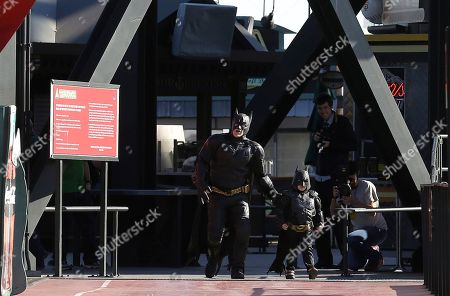 """Miles Scott, dressed as Batkid, right, walks with Batman as they look for the Penguin at AT&T Park in San Francisco, . Scott was called into service on Friday morning by San Francisco Police Chief Greg Suhr to help fight crime, as San Francisco turned into Gotham City as city officials helped fulfill the 5-year-old leukemia patient's wish to be """"Batkid,"""" The Greater Bay Area Make-A-Wish Foundation says. He was diagnosed with leukemia when he was 18 months old, finished treatment in June and is now in remission, KGO-TV reported"""