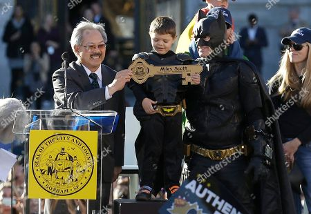 """Miles Scott, dressed as Batkid, stands next to Batman as he receives the key to the city from San Francisco Mayor Ed Lee, left, at a rally outside of City Hall in San Francisco, . Scott was called into service on Friday morning by San Francisco Police Chief Greg Suhr to help fight crime, as San Francisco turned into Gotham City as city officials helped fulfill the 5-year-old leukemia patient's wish to be """"Batkid,"""" The Greater Bay Area Make-A-Wish Foundation says"""