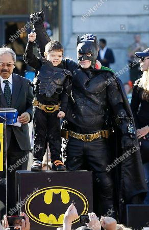 """Miles Scott, Ed Lee, Natalie Scott Miles Scott, 5, dressed as Batkid, second from left, raising his arm next to Batman at a rally outside of City Hall with Mayor Ed Lee, left, and his mother Natalie Scott, right, in San Francisco. The city of San Francisco is being rescued from paying the cost of staging the """"Batkid"""" fantasy that captured the nation's imagination. Philanthropists John and Marcia Goldman are picking up the city's $105,000 tab for allowing Scott, a Northern California boy with leukemia, to fight villains and rescue a damsel in distress as a caped crusader"""
