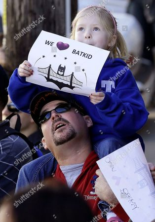 """Daniel Fry holds up his daughter Kayla, 5, as they wait for Miles Scott, dressed as Batkid, in San Francisco, . San Francisco turned into Gotham City on Friday, as city officials helped fulfill Scott's wish to be """"Batkid."""" Scott, a leukemia patient from Tulelake in far Northern California, was called into service on Friday morning by San Francisco Police Chief Greg Suhr to help fight crime, The Greater Bay Area Make-A-Wish Foundation says"""