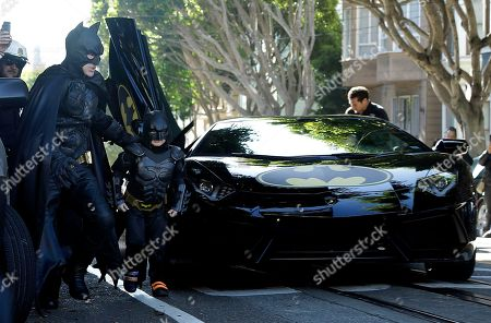 """Miles Scott, dressed as Batkid, second from left, exits the Batmobile with Batman to save a damsel in distress in San Francisco, . San Francisco turned into Gotham City on Friday, as city officials helped fulfill Scott's wish to be """"Batkid."""" Scott, a leukemia patient from Tulelake in far Northern California, was called into service on Friday morning by San Francisco Police Chief Greg Suhr to help fight crime, The Greater Bay Area Make-A-Wish Foundation says"""