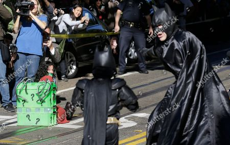 """Miles Scott, dressed as Batkid, center, walks with Batman to save a damsel in distress on the Cable Car line in San Francisco, . San Francisco turned into Gotham City on Friday, as city officials helped fulfill Scott's wish to be """"Batkid."""" Scott, a leukemia patient from Tulelake in far Northern California, was called into service on Friday morning by San Francisco Police Chief Greg Suhr to help fight crime, The Greater Bay Area Make-A-Wish Foundation says"""