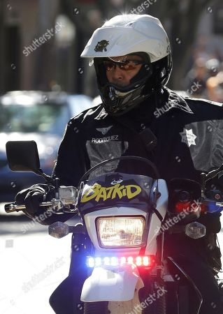 """A San Francisco Police Officer with a Batkid sign on his bike waits for the arrival of Miles Scott, dressed as Batkid, in San Francisco, . San Francisco turned into Gotham City on Friday, as city officials helped fulfill Scott's wish to be """"Batkid."""" Scott, a leukemia patient from Tulelake in far Northern California, was called into service on Friday morning by San Francisco Police Chief Greg Suhr to help fight crime, The Greater Bay Area Make-A-Wish Foundation says"""