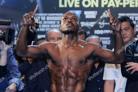 Timothy Bradley poses for photos while standing on the scale for his WBO welterweight title defense fight against Juan Manuel Marquez, in Las Vegas. Bradley will defend his belt against Marquez on Saturday