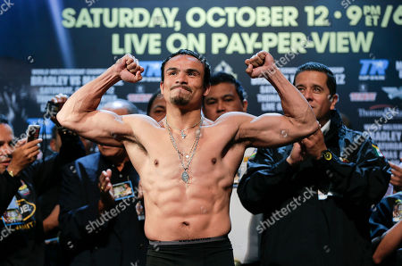Juan Manuel Marquez poses for photos as he stands on the scale during the weigh-in for the WBO welterweight title fight against Timothy Bradley, in Las Vegas. Marquez will challenge Bradley for the title on Saturday