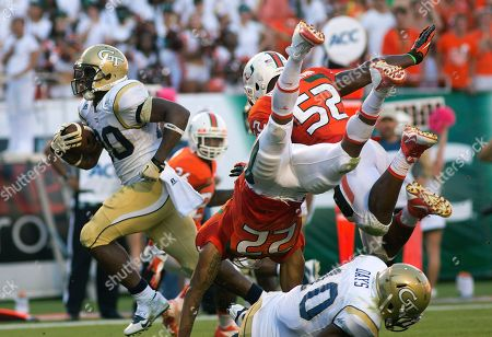 David Sims, Kacy Rogers II, Denzel Perryman Georgia Tech's David Sims, left, escapes a tackle by Miami's Kacy Rogers II (22) and Denzel Perryman (52) during the second half of an NCAA college football game in Miami Gardens, Fla., . Miami won 45-30