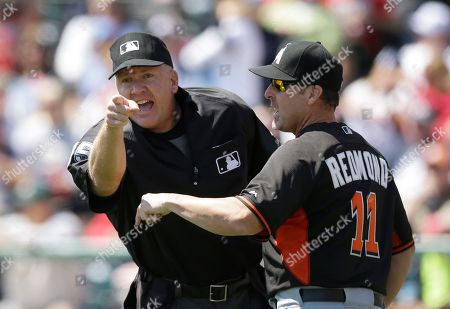 Jeff Nelson, Mike Redmond Home plate umpire Jeff Nelson is held back by Miami Marlins manager Mike Redmond as he points to Marlins third base coach Brett Butler during the first inning of an exhibition baseball game in Kissimmee, Fla., . Butler was disputing a call by Nelson