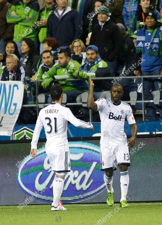 Nigel Reo-Coker, Russell Teibert Vancouver Whitecaps' Nigel Reo-Coker, right, is greeted by teammate Russell Teibert, left, after Reo-Coker scored a goal in the second half of an MLS soccer match against the Seattle Sounders, in Seattle. The Whitecaps beat the Sounders, 4-1