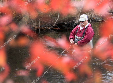 Barry George fishes for Salmon in the Merrymeeting River, in Alton, N.H. As fall arrives the fish swim up the river from Lake Winnipesaukee