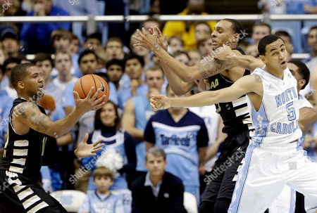 Stock Image of Marcus Paige, Duke Mondy, Tommie McCune North Carolina's Marcus Paige (5) struggles for a rebound against Oakland's Duke Mondy, left, and Tommie McCune during the first half of an NCAA college basketball game in Chapel Hill, N.C